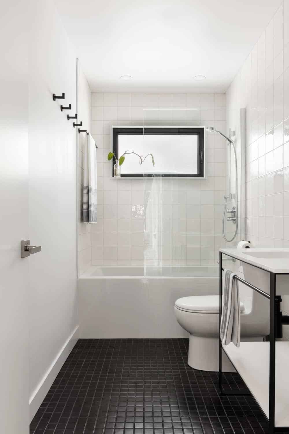This simple Scandinavian bathroom has a white ceiling, white walls, bathtub, toilet, and sink. This white theme is counterbalanced by the black elements of the floor tiles, window frame, and the dark iron housing of the sink.