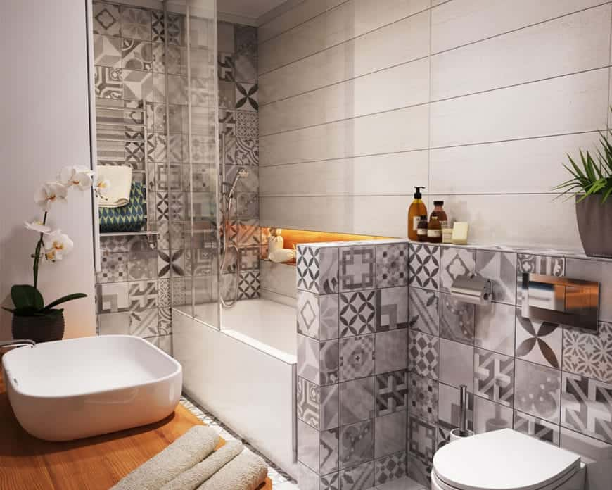 This Scandinavian-Style bathroom has gray patterned tiles on its walls and floor this is complemented by the white sink on a wood-topped vanity area as well as the white toilet and bathtub that also doubles as the shower area to save space.