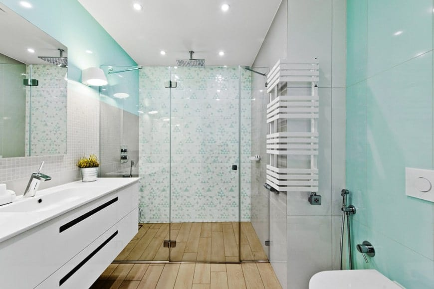 The bathroom has hardwood flooring paired with light gray walls that are accented with sleek limpet tiles and patterned tiles for the walls of the shower area. This shower area has an overhead showerhead mounted on the white ceiling.