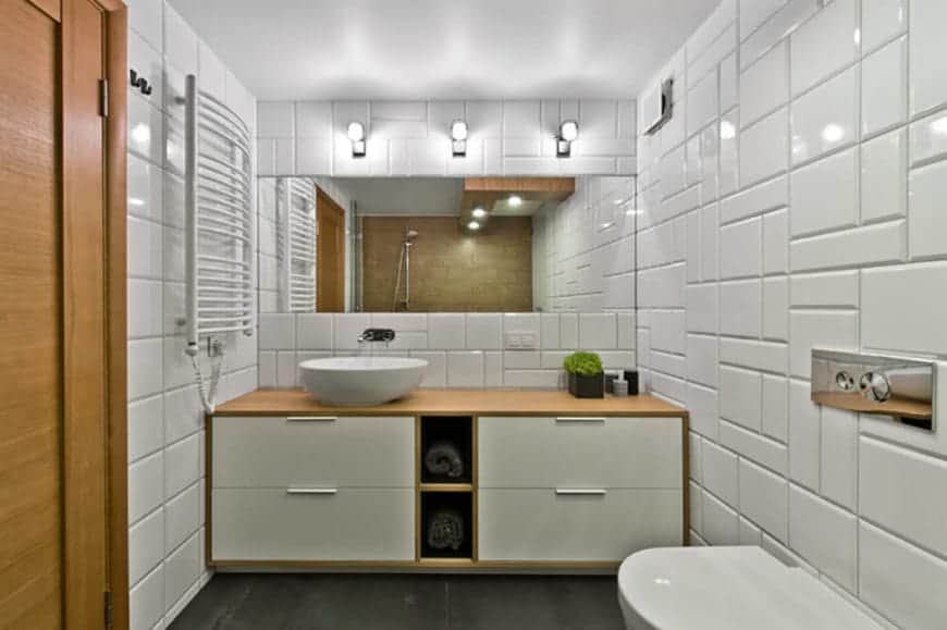 The white patterned tiles of this Scandinavian-Style bathroom is illuminated by the trio of wall-mounted modern lights above the wide vanity mirror. The white tiles are contrasted the wooden vanity area with built-in drawers and shelves for the towels.