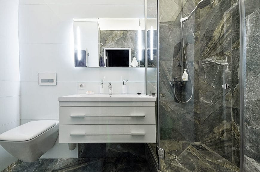 The walls and floor of the shower area are made up of gray marble that has brownish accents. These accents give it an illusion of texture that contrasts with the smooth white walls and drawers of the sink area topped with a wall-mounted mirror.