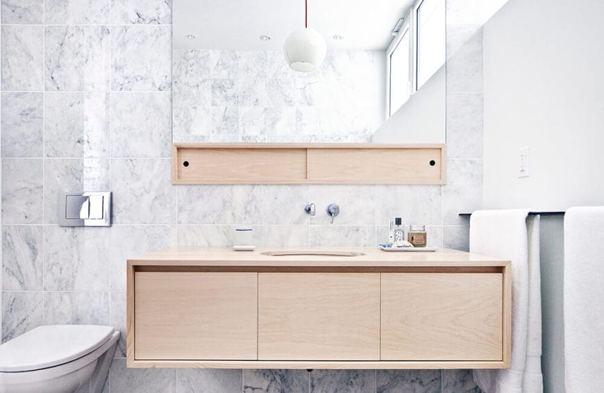 The white sink of this vanity area has wall-mounted wooden housing with built-in drawers with a space beneath the countertop to act as drawer handles. This wooden element is paired with the wooden bracket holding up the vanity mirror on the white marble wall.