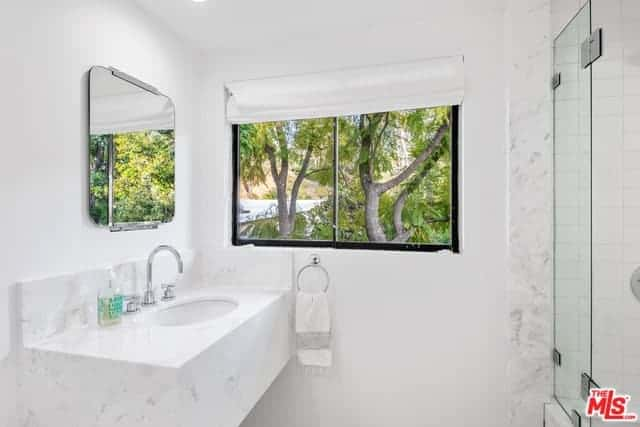 This Scandinavian-Style bathroom has white walls, a white ceiling, and a white vanity area that has a white sink built into a white marble housing that extends to a backsplash. This white monotony is broken by the scenery of nature outside the window.