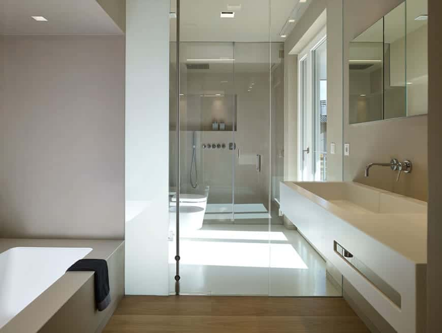 This Scandinavian-Style master bathroom is divided into three sections separated by glass doors. The first one is the vanity area with a white sink across from the bathtub built-into the wall. The second is the toilet area next to the shower area.