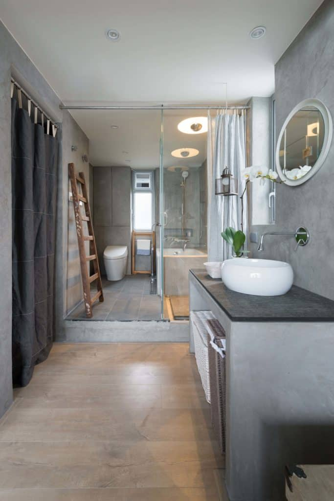 The vanity area is made of stone built into the wall and has a black countertop that contrasts the small sink on top of it. The gray-walled bathtub area is separated by a glass wall and has a rustic wooden ladder to be used as a towel rack.