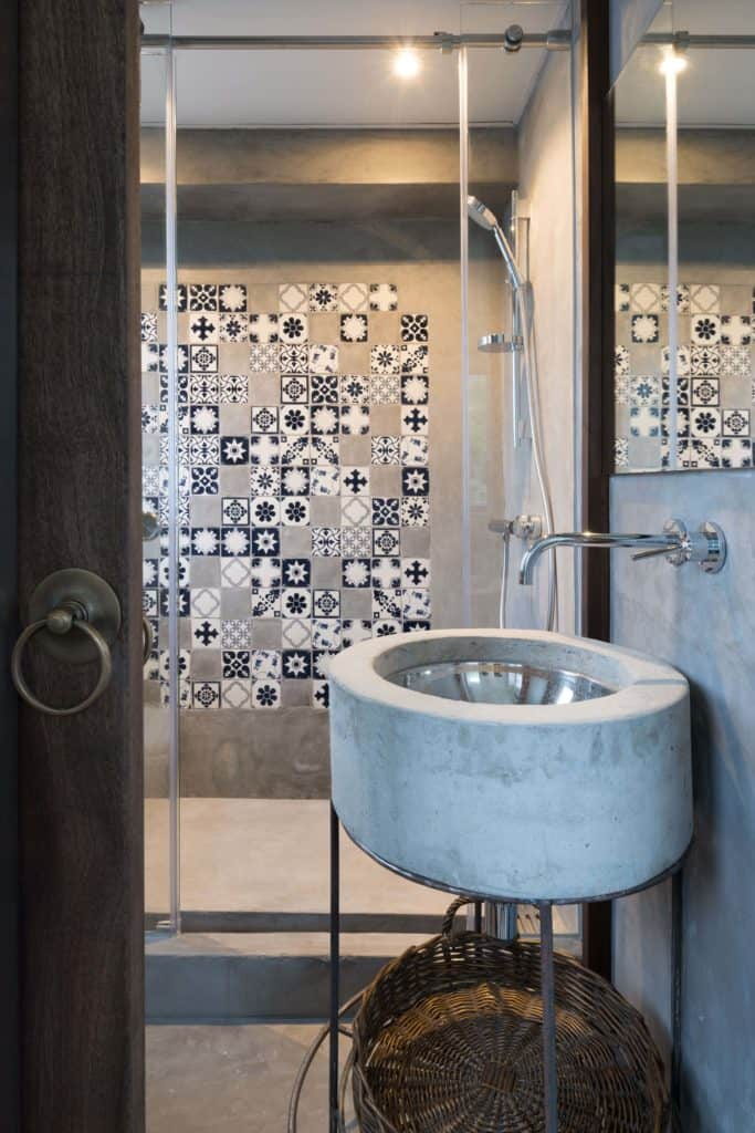This is a small Scandinavian-Style bathroom that has a metallic circular sink built into a stone structure that is held up by iron legs. The same stone finish is given to the walls and floor and is contrasted with small patterned tiles on the wall of the shower area.