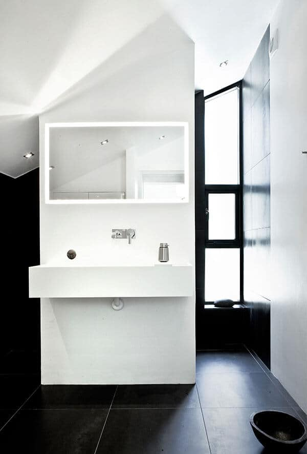 The dark tiles of the floor and walls are contrasted by the sleek whiteness of the vanity area. The white sink is built into a white piece of wall that extends to the white shed ceiling and holds a wall-mounted rectangular vanity mirror with backlight.