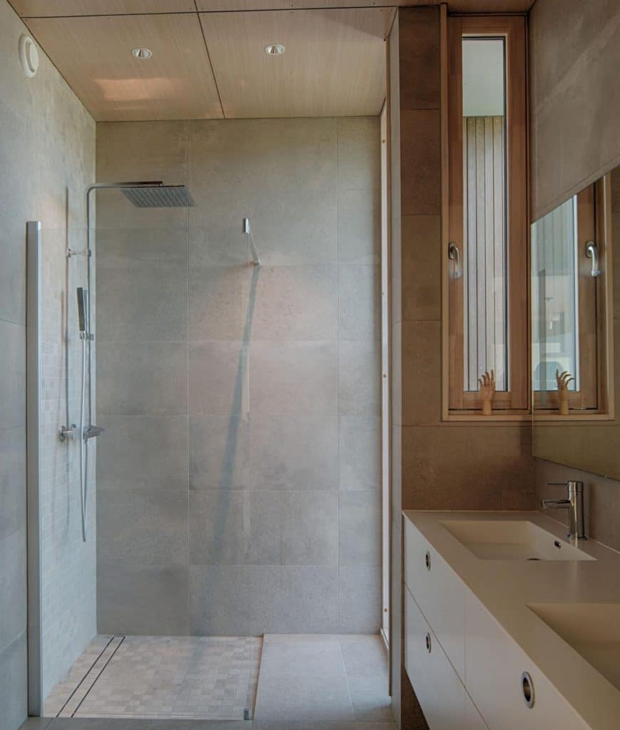 The shower area is separated from the rest of the Scandinavian-Style bathroom by a glass door which blends seamlessly with the gray walls. It has modern shower fixtures that match with the faucets of the vanity area that has a white countertop.
