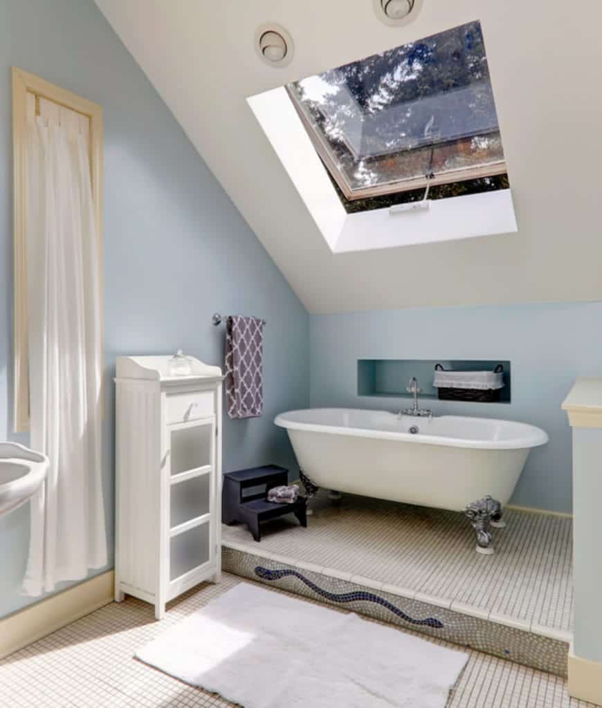 This chic Scandinavian-Style bathroom has sunny demeanor with its low shed ceiling paired with a ceiling window that illuminates the white tiles with sunlight. The freestanding bathtub with elegant legs is placed against the low end of the ceiling against a limpet wall.