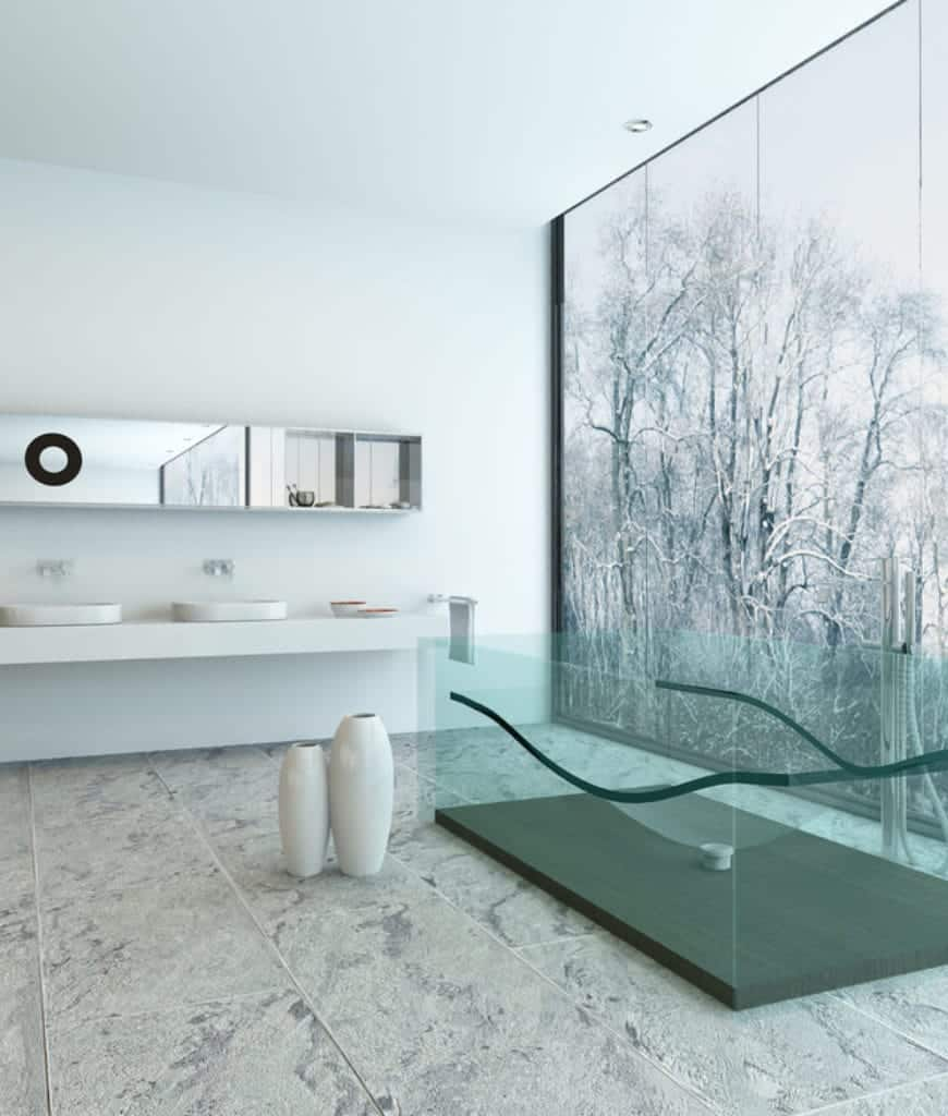 The highlight of this Scandinavian-Style bathroom is the glass transparent bathtub that has a greenish tint. This is paired with a massive window that shows the nature outside. The white vanity area seems to blend into the white walls topped with a long and narrow vanity mirror.