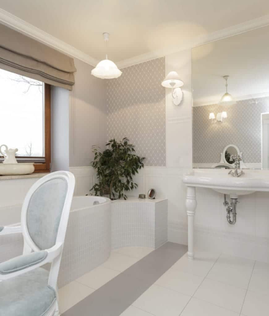 This is Scandinavian-Style bathroom with a few elegant details added to its simple brightness. The white sink has stylish ceramic legs holding it up. The white bathtub that is built into the wall next to a window is topped by a pendant light that looks like a flower.