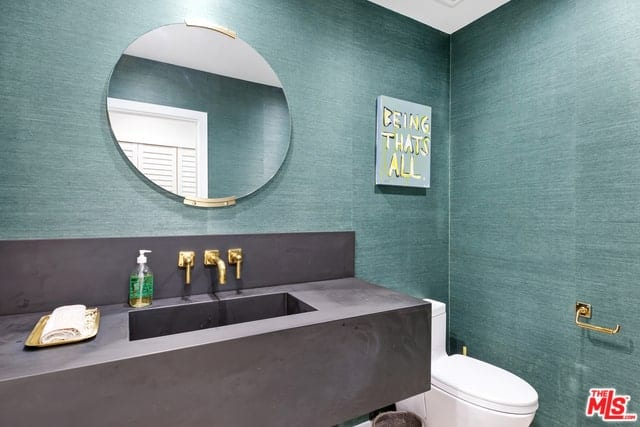 This bathroom has walls covered in sea green wallpaper that matches well with the dark gray housing of the sink area extending to the backsplash. This contrasts with the golden fixtures of the bathroom as well as the golden brackets of the circular vanity mirror.