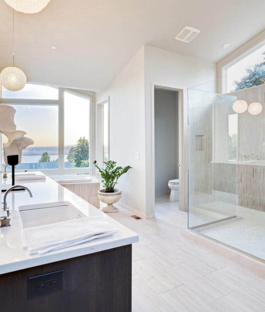 This is a wide and wiry bathroom with three sections. The shower area is behind a glass box while the toilet area is in a small room behind a door. The bathtub area is next to a massive glass window that offers an amazing view of the outside beauty.