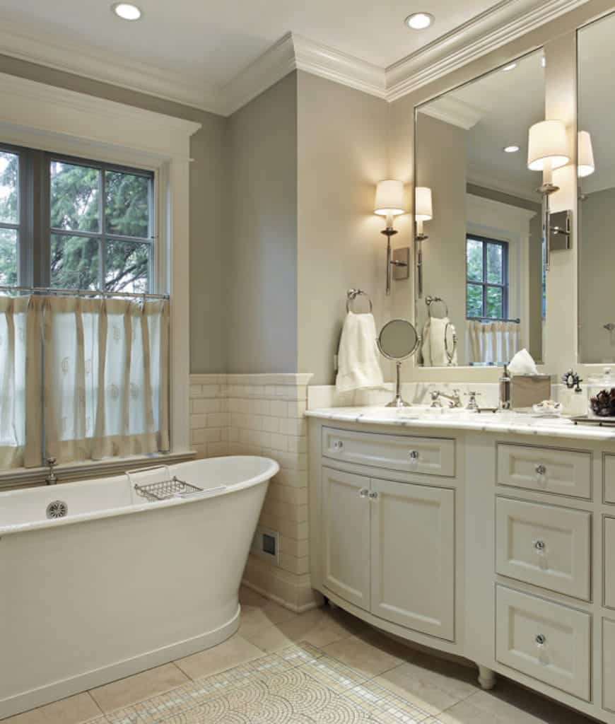 The freestanding white bathtub is placed into a nook beside the curtained French windows. The vanity area is built into the gray wall with its white wooden cabinets and drawers that have crystal handles illuminated by the pin lights of the white ceiling.