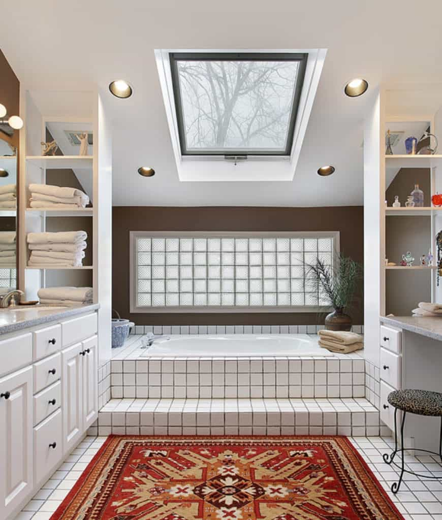 This is a Scandinavian-Style bathroom dominated by patterns and lines. The lines come from the white tiles of the floor running to the bathtub and around it. The tiles are paired with black grout to emphasize the lines and this is contrasted by a colorful patterned area rug in the middle of the floor.