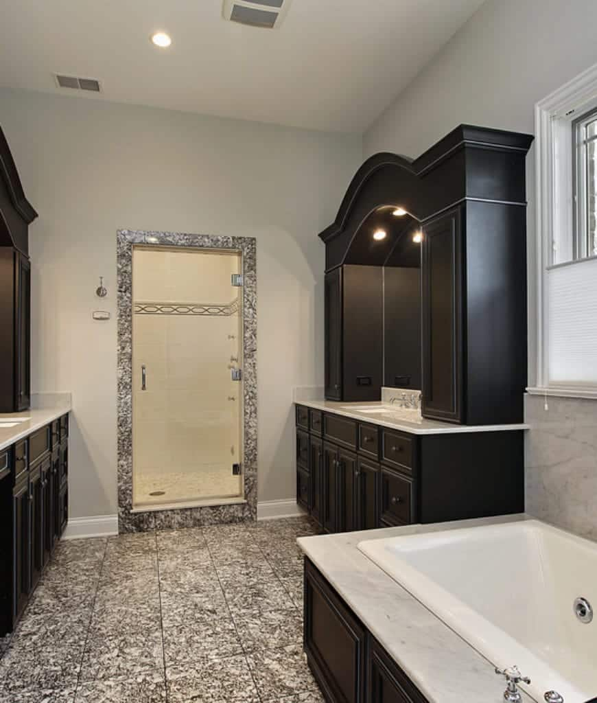 The floor tiles have a gray and white chaotic pattern that is contrasted by the plain dark wooden elements of the wooden structures housing the two vanity areas and the bathtub. They stand out against the white wall and the white ceiling.