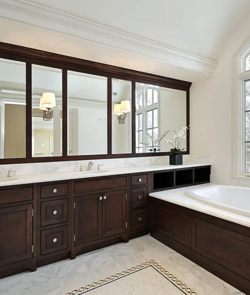 The massive wooden structure of this Scandinavian-Style master bathroom makes up the length of the vanity area and extends all the way to the bathtub housing by the window. This is paired with a massive wall-mounted vanity mirror with wooden frames.