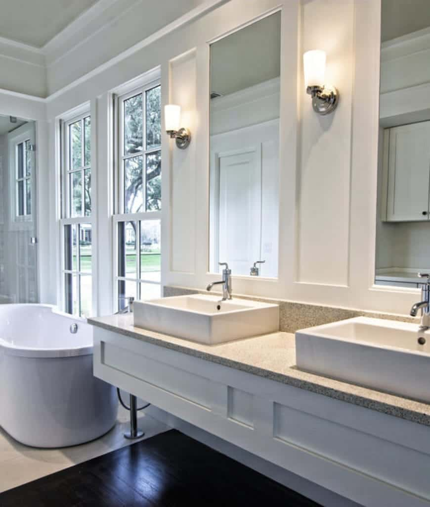 The tall vanity mirrors are built into the white wooden finish of the walls and flanked by modern wall-mounted lamps that match the faucets. The sinks of the vanity area match with the freestanding bathtub by the French windows.