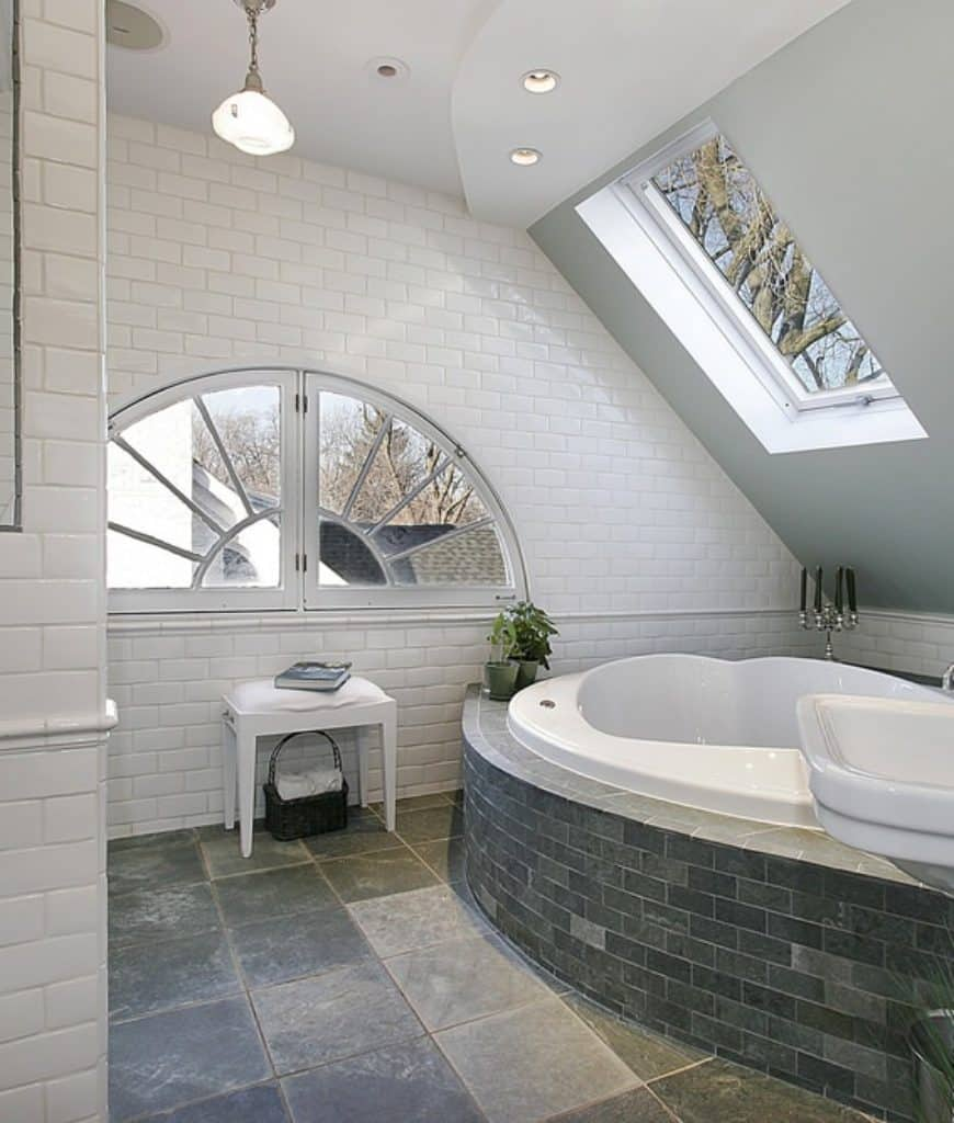 This Scandinavian-Style bathroom has a low shed ceiling with a window above the massive bathtub built into white walls surrounded by gray tiles fixed in a brick wall design. These tiles match those of the floor that contrasts the white stone walls.
