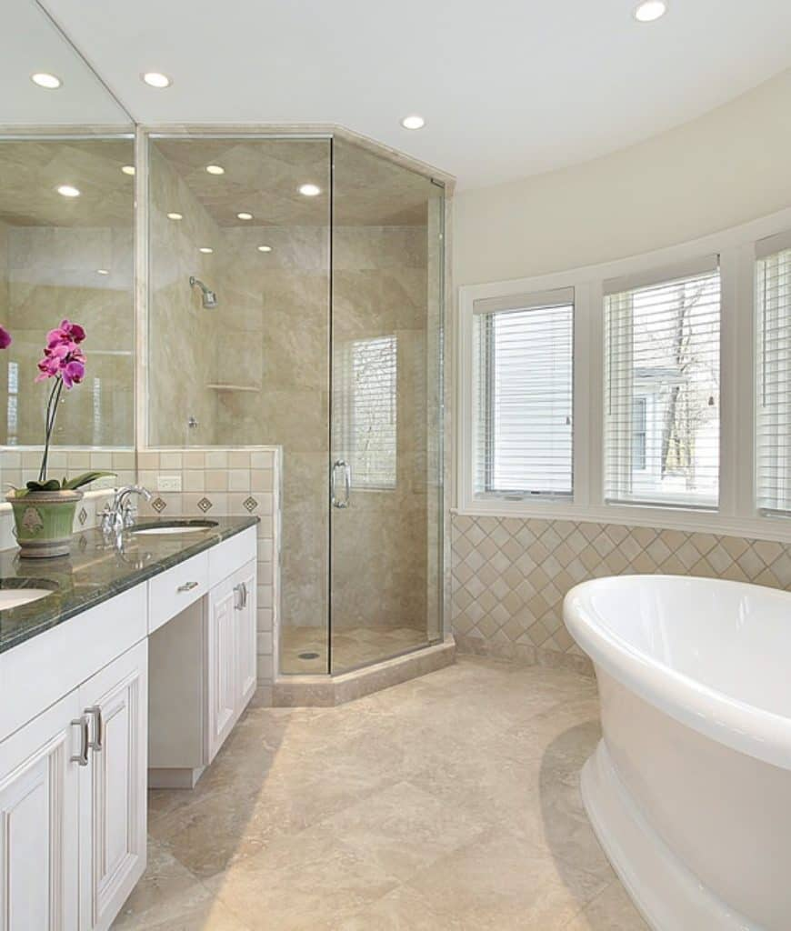 This Scnadinavian-Style bathroom is predominantly beige in color with its beige marble flooring and beige tiles adorning the walls. The shower area is through a glass door and has walls and floor that match the beige marble.