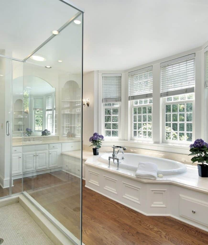 The centerpiece of this bathroom is the bathtub that is fixed into an elegant white wooden structure that has a beige marble countertop matching those of the vanity area's countertop. The bathtub is illuminated by a row of French windows beside it.