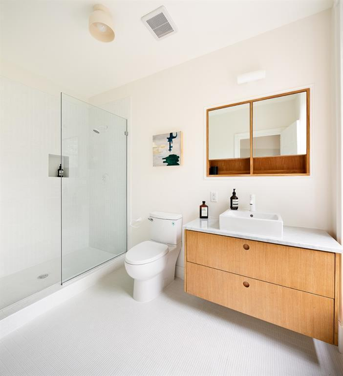 The shower area of this Scandinavian-Style bathroom has white-tiled walls and flooring and is separated from the rest of the bathroom with a glass wall. The vanity area has a wall-mounted mirror framed with wood and built-in shelves that match the drawers of the sink.