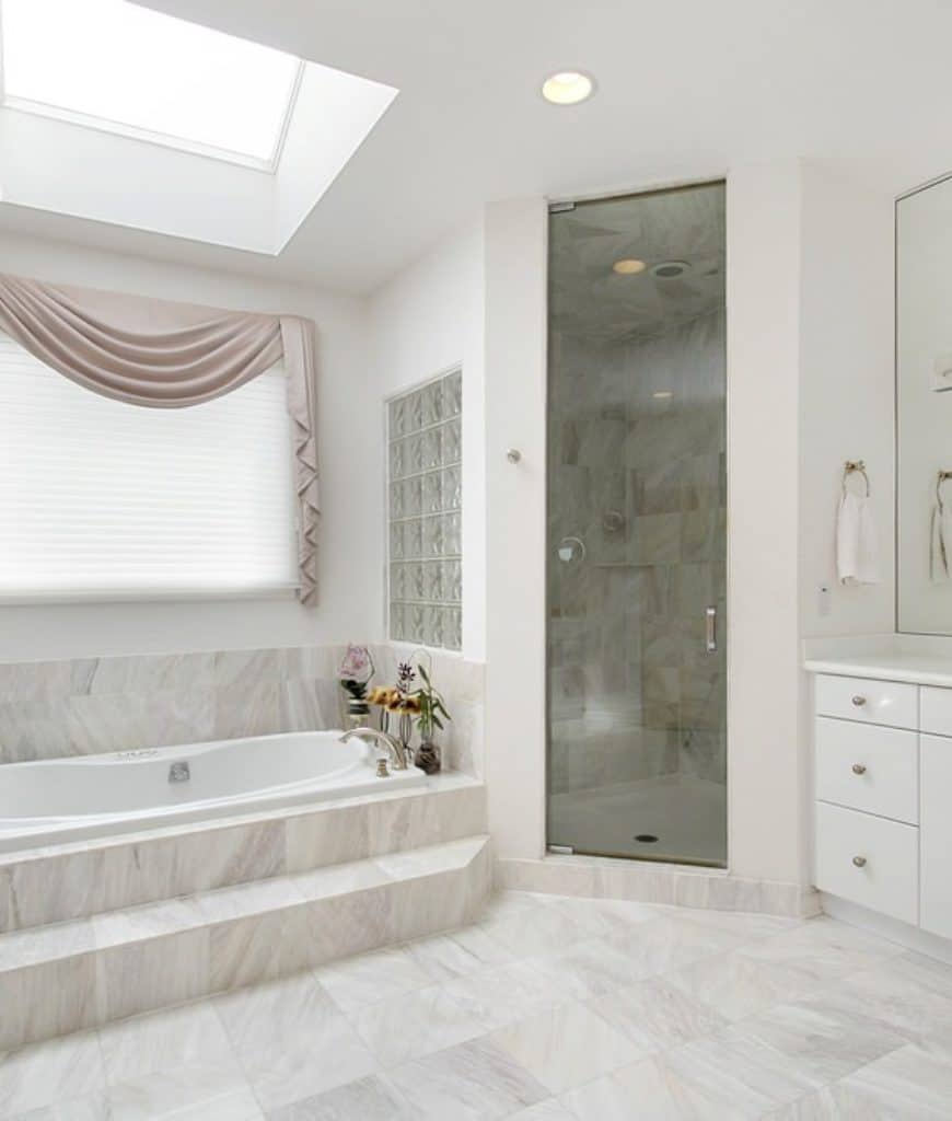 This is a predominantly white bathroom with its white marble flooring and white walls which are brightened up by the sunroof on the white ceiling. The white bathtub is inlaid with the same white marble as the flooring as well as its backsplash.