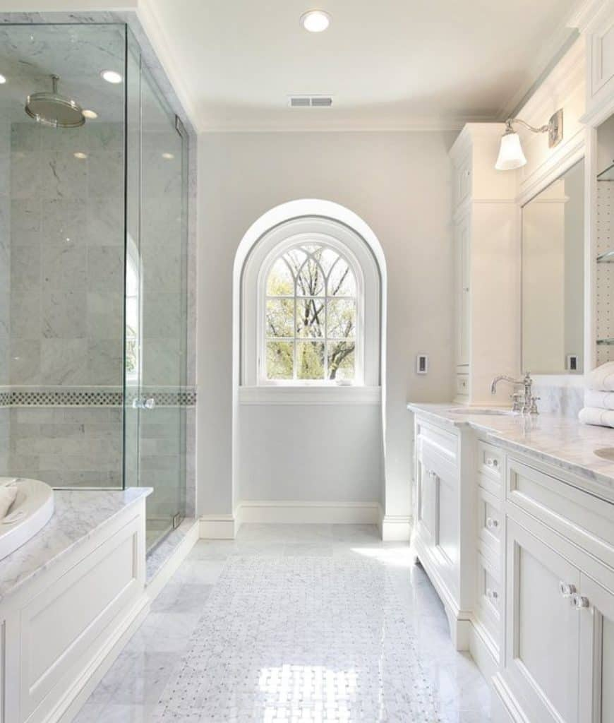 The wall of the vanity area is dominated by a massive white wooden structure with elegant drawers and cabinets with crystal handles. This seems to blend into the white walls that are reflected by the sleek white flooring of this Scandinavian-Style bathroom.