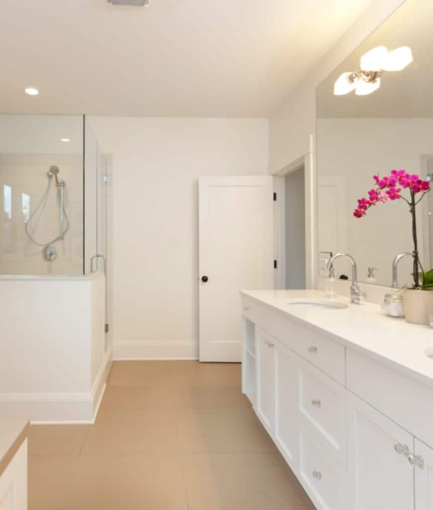 This is a white white-walled Scandinavian-Style bathroom that has beige floor tiles making the built-in cabinets and drawers of the vanity area stand out. The lamp that is mounted on the wide vanity mirror illuminates the white countertop and the white ceiling.
