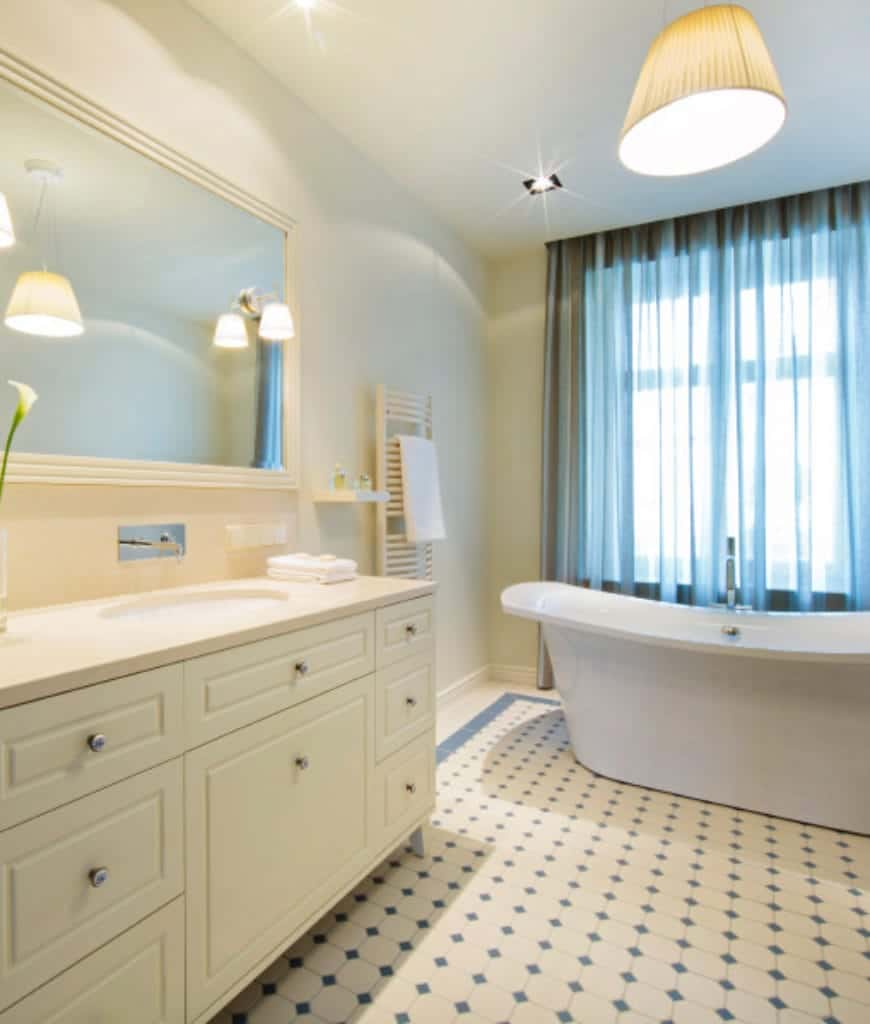 The white tiles of the floor have a pattern of sea-green diamonds on it that match with the curtains of the tall windows beside the freestanding bathtub. Over this bathtub is a pendant light with a beige cover that matches with the wall-mounted lights of the vanity area.