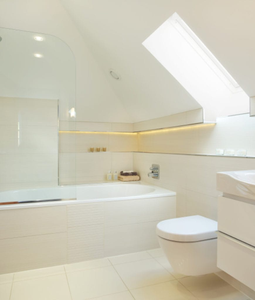 This Scandinavian-Style bathroom has white shed ceiling with a window above the white floating toilet. Beside the toilet is a white bathtub built-into the corner of the room with the same tiles as the floor and wall. It is partially covered by a glass wall.