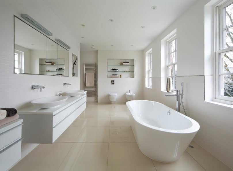 This is a wide and airy Scandinavian-Style bathroom due to its trio of windows lining the wall that illuminates the white freestanding bathtub with natural light. Across the bathtub is a floating vanity area with two sinks and topped with a wide wall-mounted mirror.