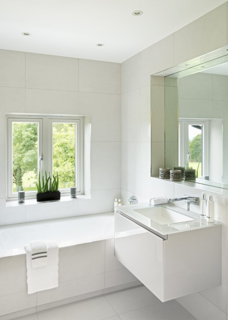 This is a white and modern Scandinavian-Style bathroom with a sleek floating vanity area that has a glass countertop paired with a modern faucet. Above this is a mirror embedded into the white wall in a square cove. Besides the vanity is the white bathtub that is built into the corner with the same white tiles on the floor.