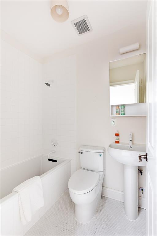 The bathroom's white tiles are illuminated by a flush mount ceiling light in the middle of a white ceiling. The small vanity area has a white sink with ceramic stand and wall-mounted mirror. Above the mirror is a wall-mounted lamp that seems to blend into the white walls.