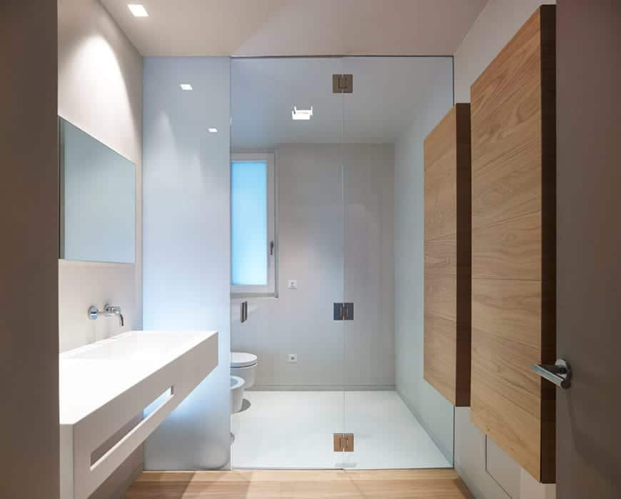 The white walls of this Scandinavian-Style bathroom are accented with thick wooden planks overlayed on the wall. This accent matches the hardwood floor of the white vanity area which is separated from the toilet area by a glass door.