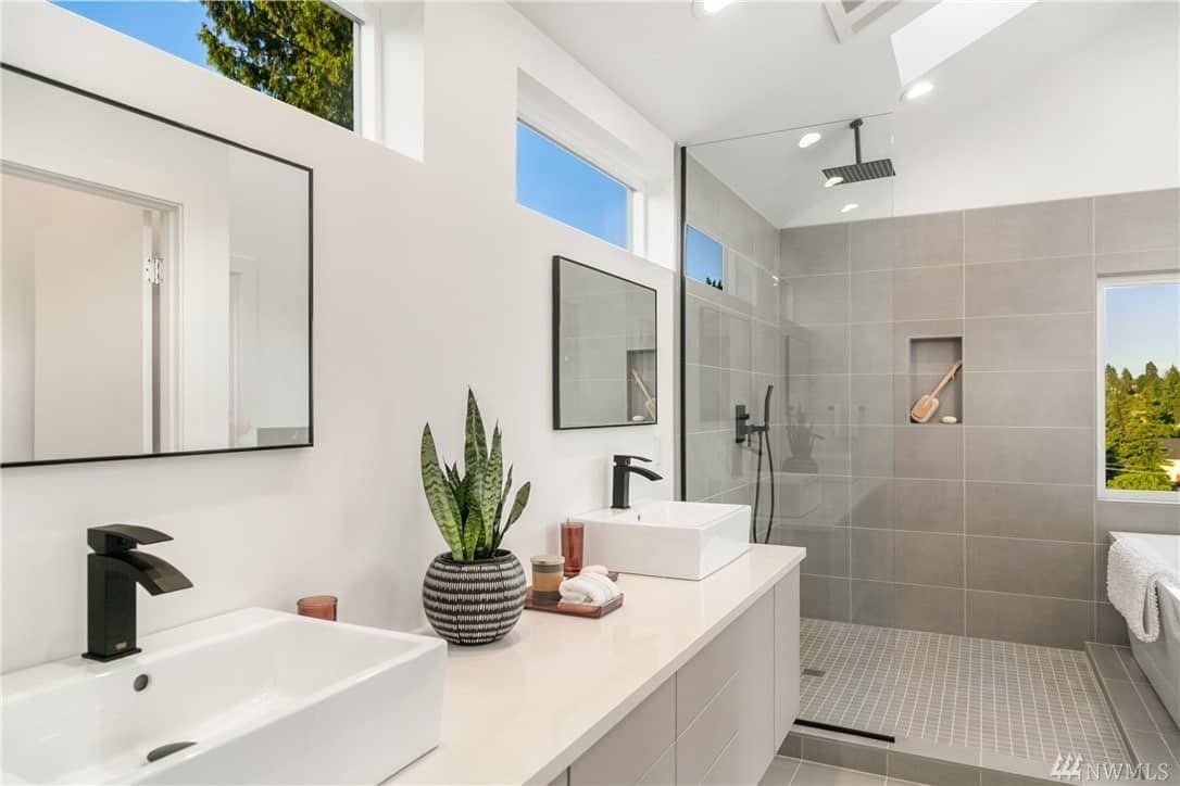 The shower area has a dark overhead showerhead that matches with the faucets of the bathroom. This shower area has gray tiles on the walls that contrast with the white wall of the vanity area that has two sins and a pair of wall-mounted vanity mirrors.