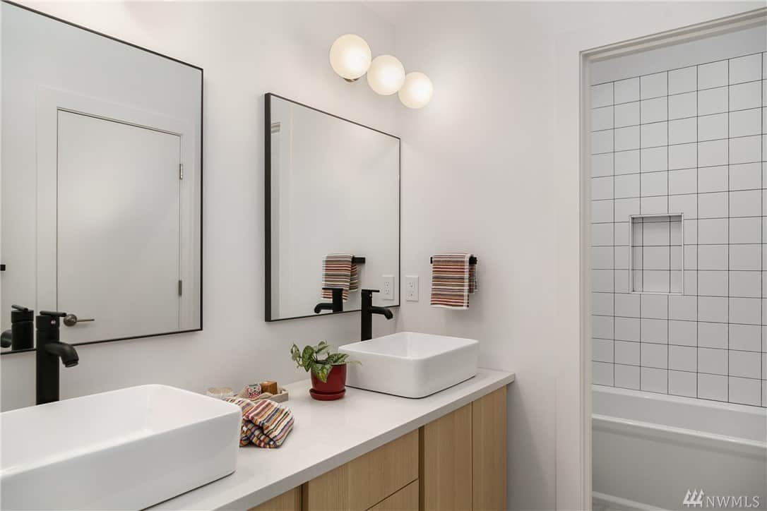 There are two vanity mirrors in this Scandinavian-Style bathroom with a matching wall-mounted row of spherical lamps above. These lamps illuminate the white sink that blends with the white countertop contrasted by the charming black faucets.
