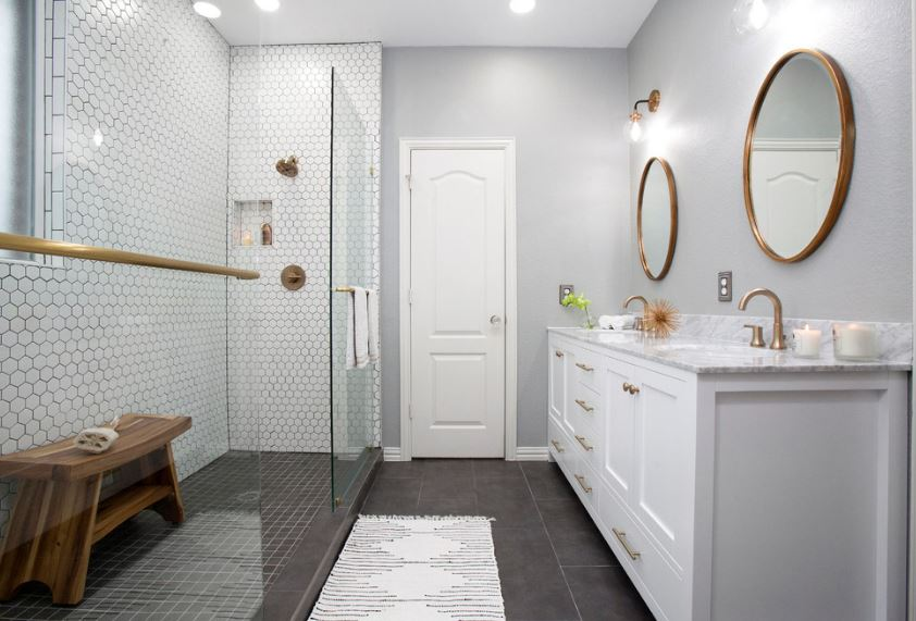This Scandinavian-Style bathroom's shower area is bordered from the rest of the bathroom with a glass wall. It has black tile for the floor and white hexagonal tiles for the walls. This contrasts the light gray walls of the rest of the bathroom.