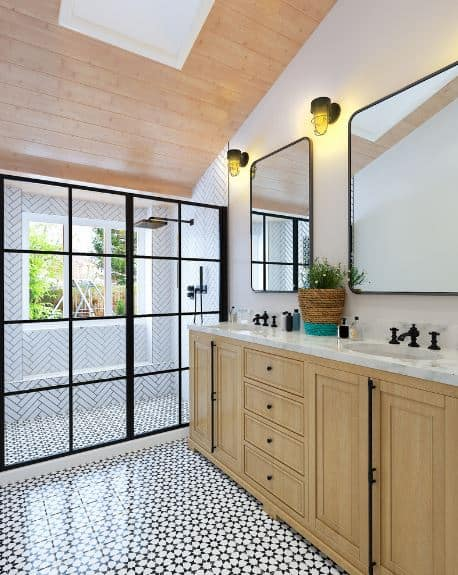 This bathroom is dominated by the intricate patterns of the black and white tiles of the floor paired with the patterns of the white-tiled walls of the shower area. The shower area has a glass door with black frames that match the frames of the wall-mounted mirrors of the vanity area.