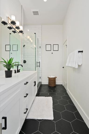 The black hexagonal tiles of the floor are paired with white grout to emphasize the lines of the tiles. This black and white theme is applied to the rest of the Scandinavian-Style bathroom with its black handles on white drawers and black fixtures on white walls.