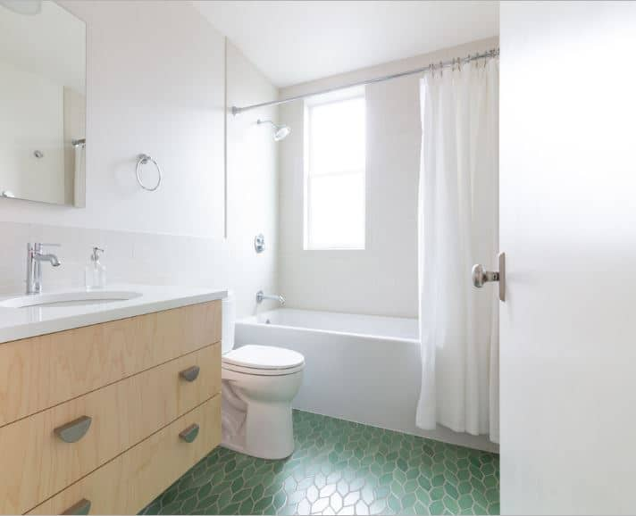 This Scandinavian-Style bathroom has a simple white and bright theme that is contrasted by the charming green tiles of the floor that has leafy braid-like patterns. These floor tiles make the white toilet and white bathtub stand out in their brightness.
