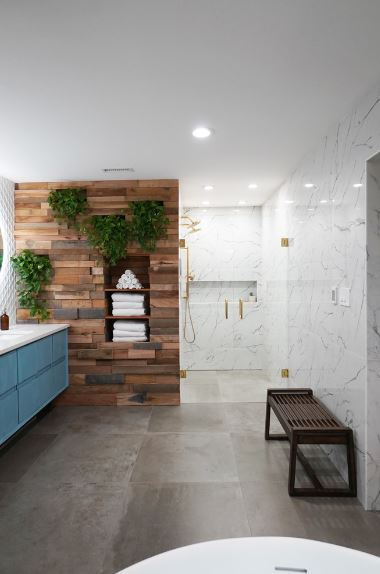 This is a master bathroom with lots of floor space in the vanity area. The floor has gray tiles that make it look industrial. This is paired with white marble walls that extend all the way to the shower area that has a stone wall accented with various wood planks.