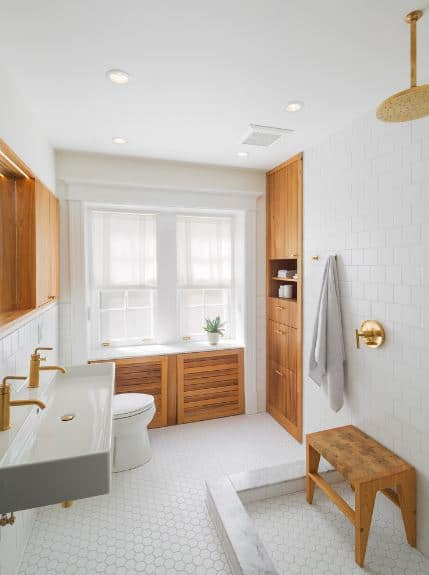 The elements of gold and wood stand out against the white ceiling and white-tiled floors and walls. The gold elements are seen on the faucets, overhead shower, and their fixtures. The wooden elements are applied to the cabinets, drawers and charming little bench in the shower area.