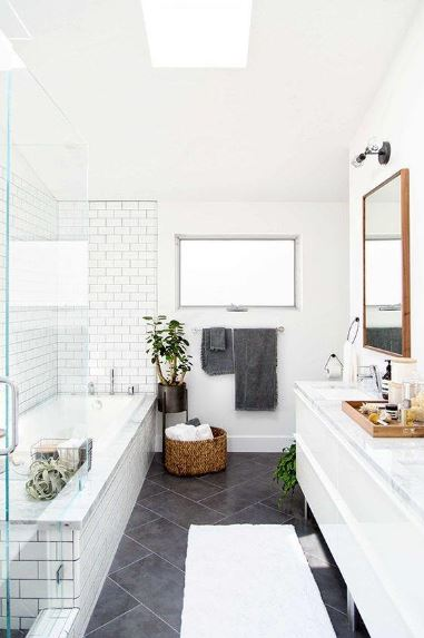 The bathtub is fixed into the corner of the bathroom with white tiles paired with black grout and arranged in a brick wall pattern. This is reciprocated by the black tiles of the floor paired with white grout. This floor stands out against the white walls and ceiling.