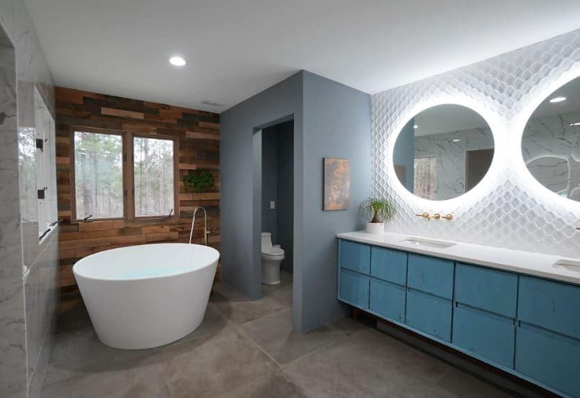 This charming white-ceilinged bathroom has a quaint circular freestanding bathtub by the window of the wooden wall. next to this area is the toilet which is enclosed in gray walls that matches the gray floor tiles. The vanity stands out with its light blue drawers and mirrors with backlight.