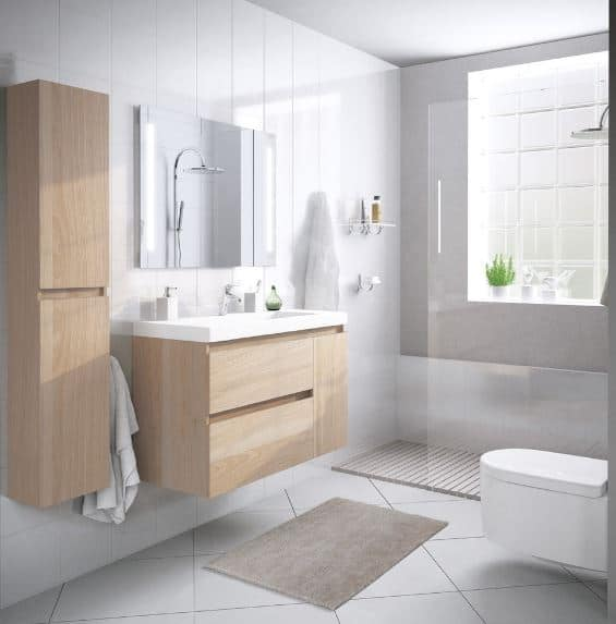 This bathroom has a shower area illuminated by a frosted glass window and brightens up the white tiles of the walls and floor which is topped with gray non-slip area rugs for safety. Both the wooden vanity area and white toilet are of a floating design to maximize space.