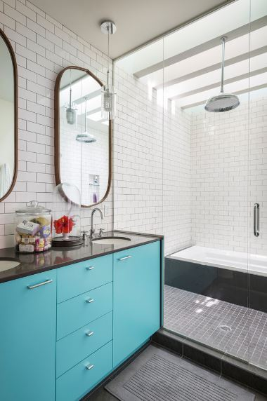 This Scandinavian-Style bathroom has charming built-in limpet drawers and cabinets of the vanity area that has a black countertop with two sinks paired with oblong wall-mounted mirror. This is besides a glass door leading to the shower area and bathtub with black tiles.
