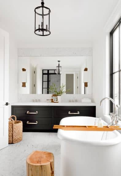 The black built-in drawers of the vanity area stand out against the white countertop and walls as well as the floor of this Scandinavian-Style bathroom. The white bathtub is paired with rustic wooden elements of the bath caddy and the tree stump stool beside it.