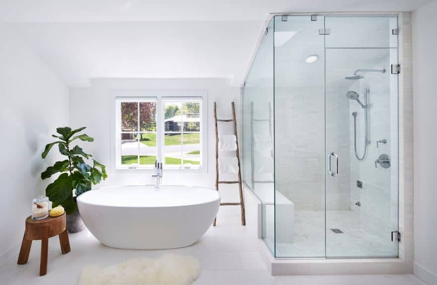 The shower area is walled in with glass and white tiles separating it from the rest of the Scandinavian-Style bathroom. The freestanding bathtub is situated beside a window and sandwiched by aa rustic wooden ladder towel rack and a potted plant.
