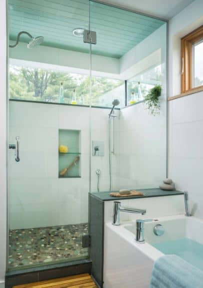 The shower area of this Scandinavian-Style bathroom has colorful random floor tiles and white walls that are topped by glass windows that offer a view of the outside. This shower area is separated from the bathtub area with a glass door and wall fixed into the bathtub housing.